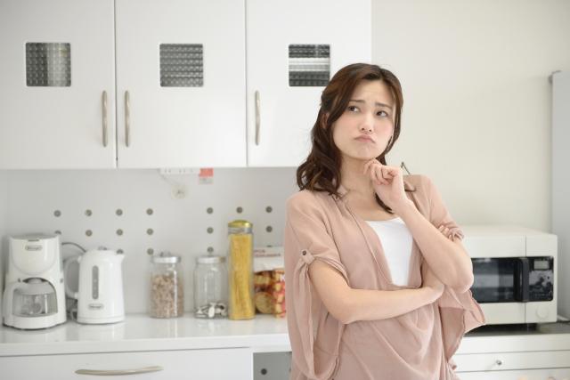 台所で悩む女性