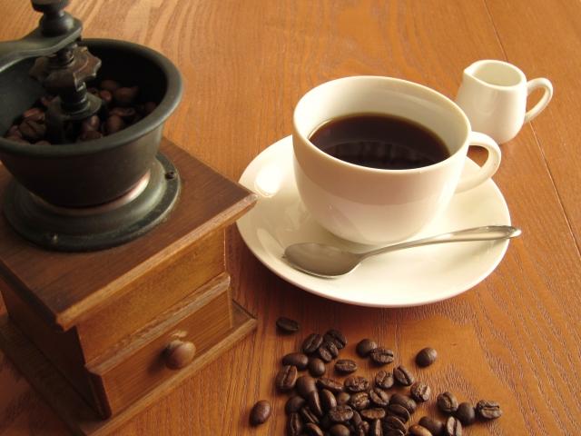 コーヒー豆とコーヒーミルとカップに入ったコーヒー